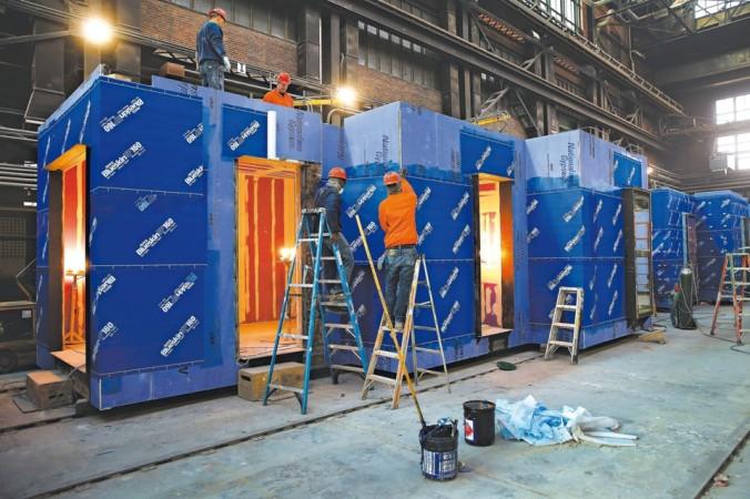 Operários aplicam impermeabilização em módulo